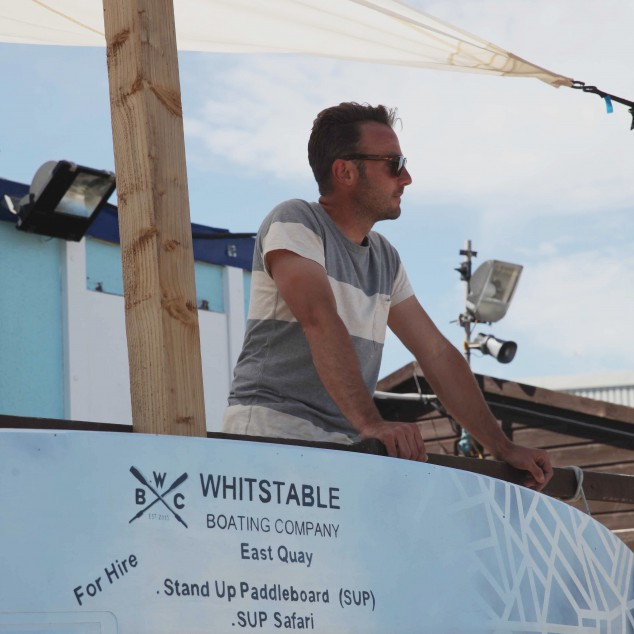 Patrick, owner of The Whitstable Boating Company, wearing Universal Works T Shirt and Monokel Sunglasses. ©James Marsh